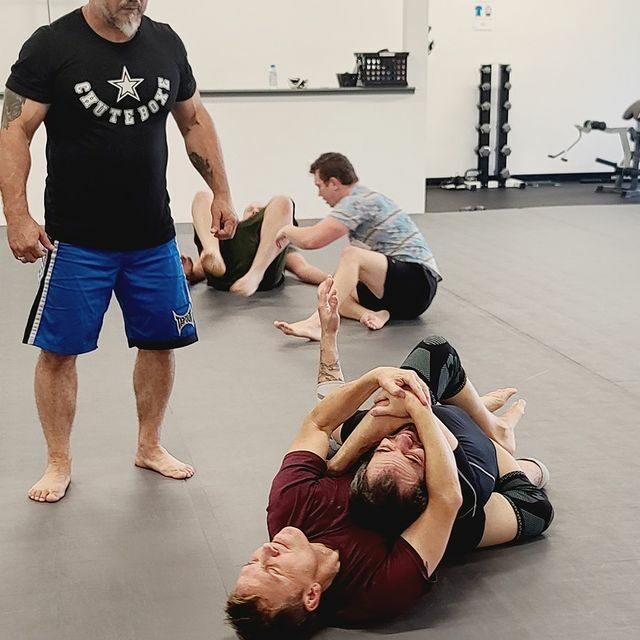 athletes training jiu jitsu choke out with back control